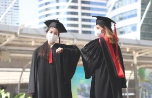 College graduates wearing medical masks.